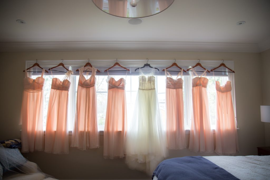 wedding and bridesmaid dresses hanging in front of window